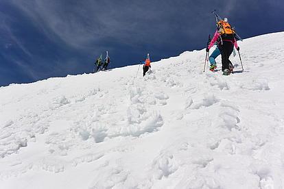 Steiler Gipfelaufstieg mit Steigeisen und den Ski am Rücken