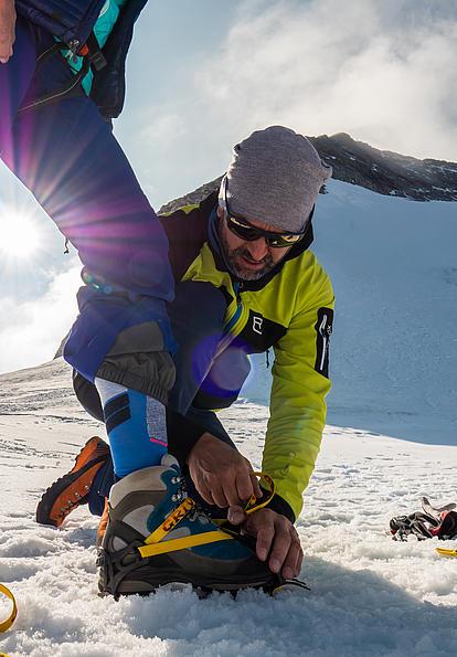 Steigeisen werden angelegt und vom Bergführer kontrolliert