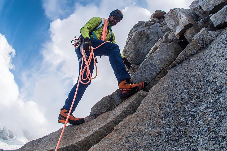 Bergführer sichert mit Seil am schmalen Grat
